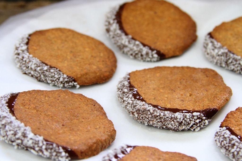 biscoito de coco e amendoim banhado no chocolate com coco seco secando papel manteiga - amor pela comida