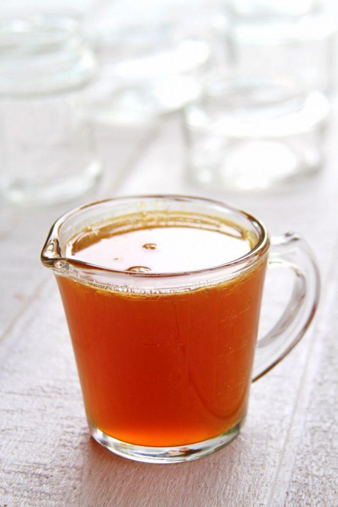 Calda de laranja dentro de jarra de vidro sobre mesa branca