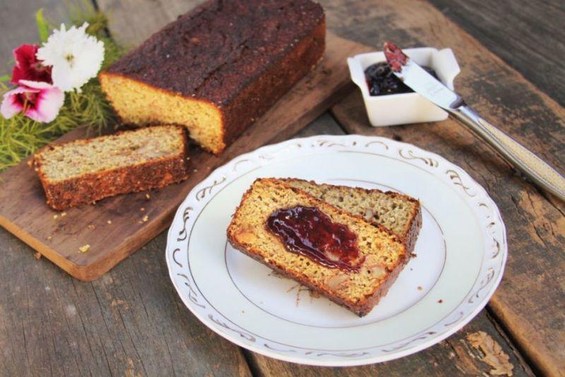 Pão fatiado dentro prato coberto com geleia sobre mesa de madeira escura