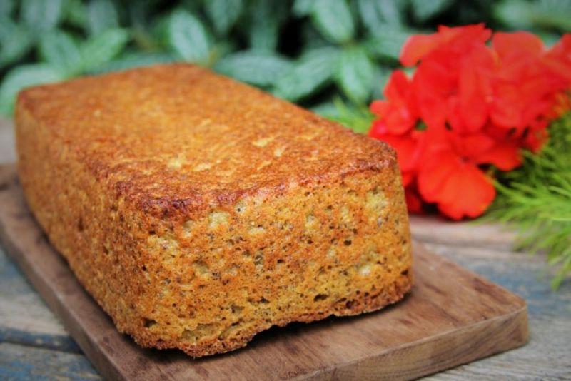 Pão amarelo sobre mesa de madeira com folhagens de fundo e flor vermelha decorativa