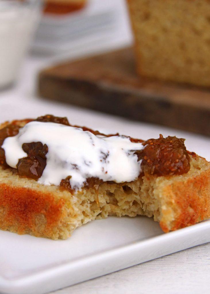 Fatia de pão de forma com geleia de figo e creme de leite em um prato branco
