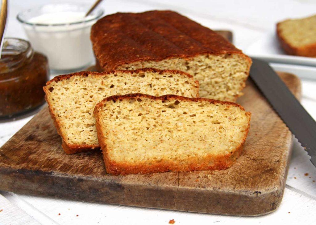 Pão de forma fatiado sobre tábua de madeira em uma mesa branca
