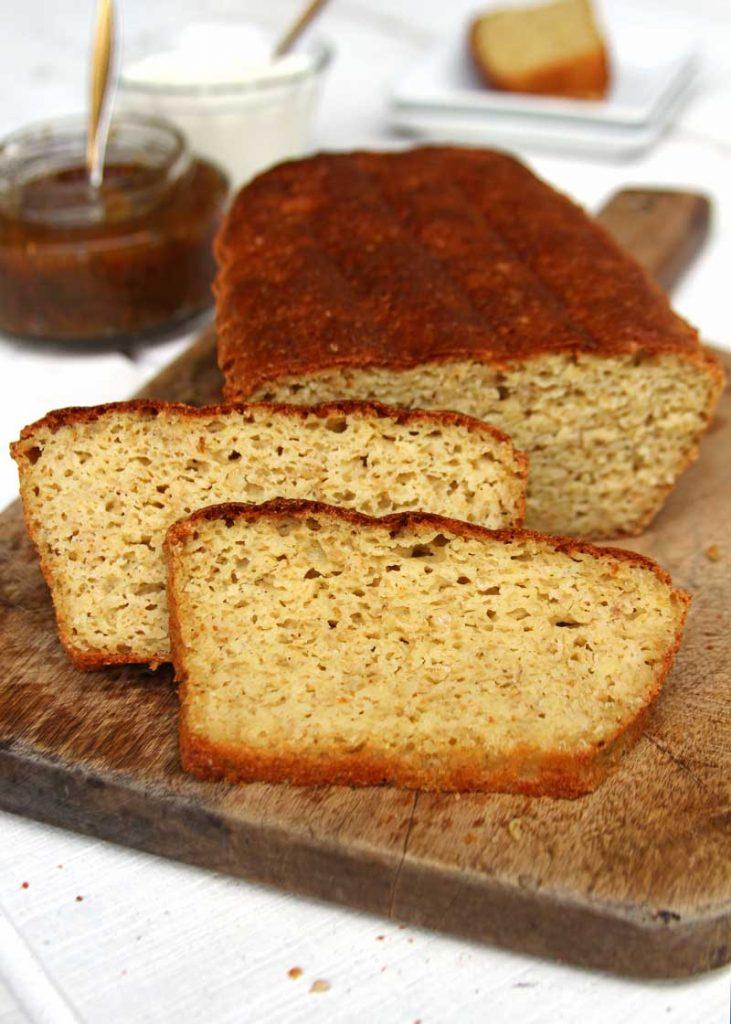 Pão de forma fatiado sobre tábua de madeira em mesa branca