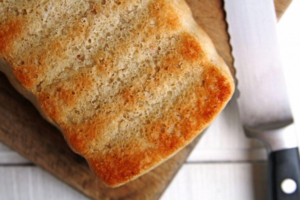 Pão sobre tábua de madeira com uma faca ao lado em uma mesa branca