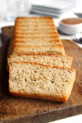 Pão de forma sem glúten fatiado sobre tábua de madeira em uma mesa branca
