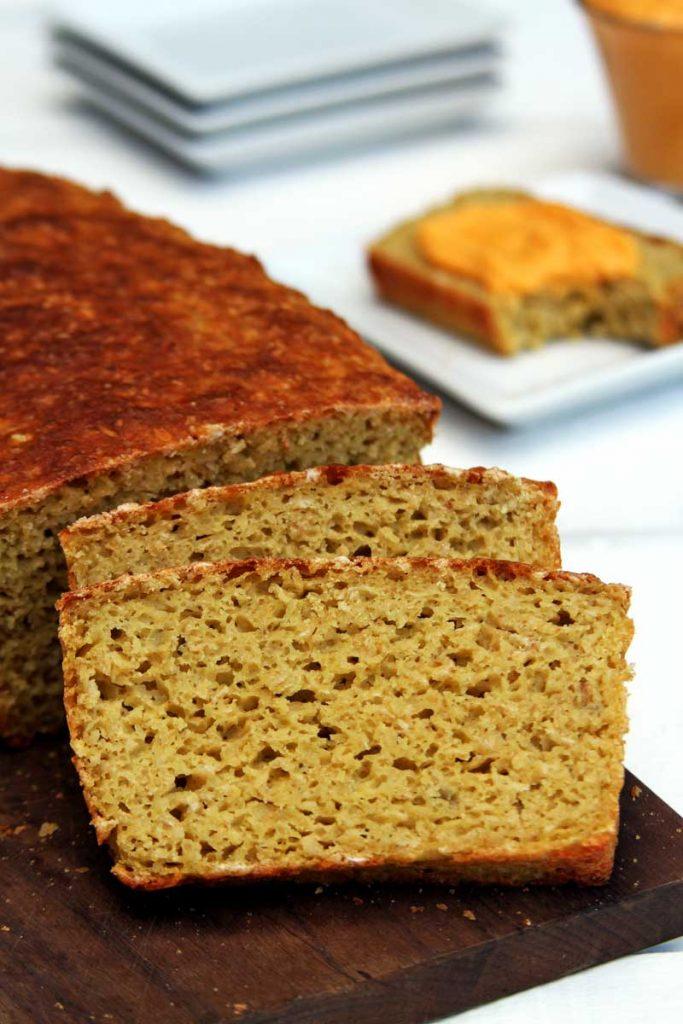 Pão de forma fatiado sobre tábua marrom e mesa branca