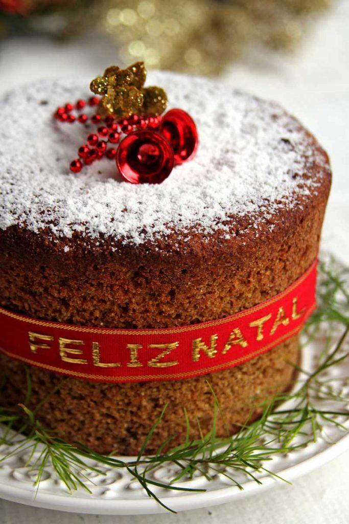 Panetone decorado com açúcar confeiteiro, fita vermelha e decoração de natal