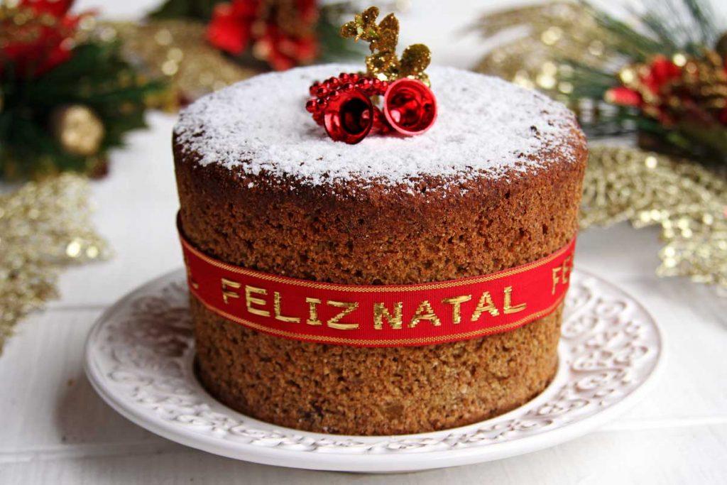 Panetone sobre prato branco, decorado com fita vermelha, açúcar confeiteiro e enfeites de natal