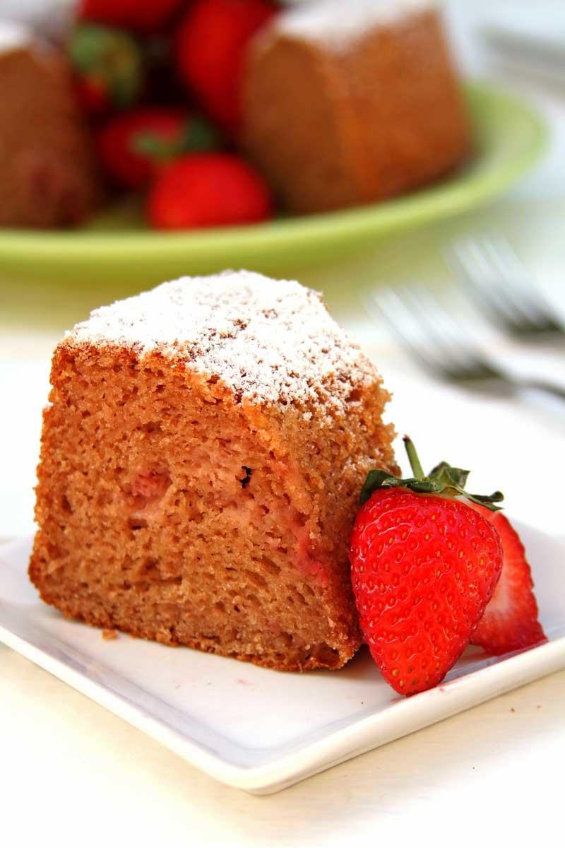 pedaço de bolo de morango com um pouco de açúcar confeiteiro por cima e decoração de morango natural
