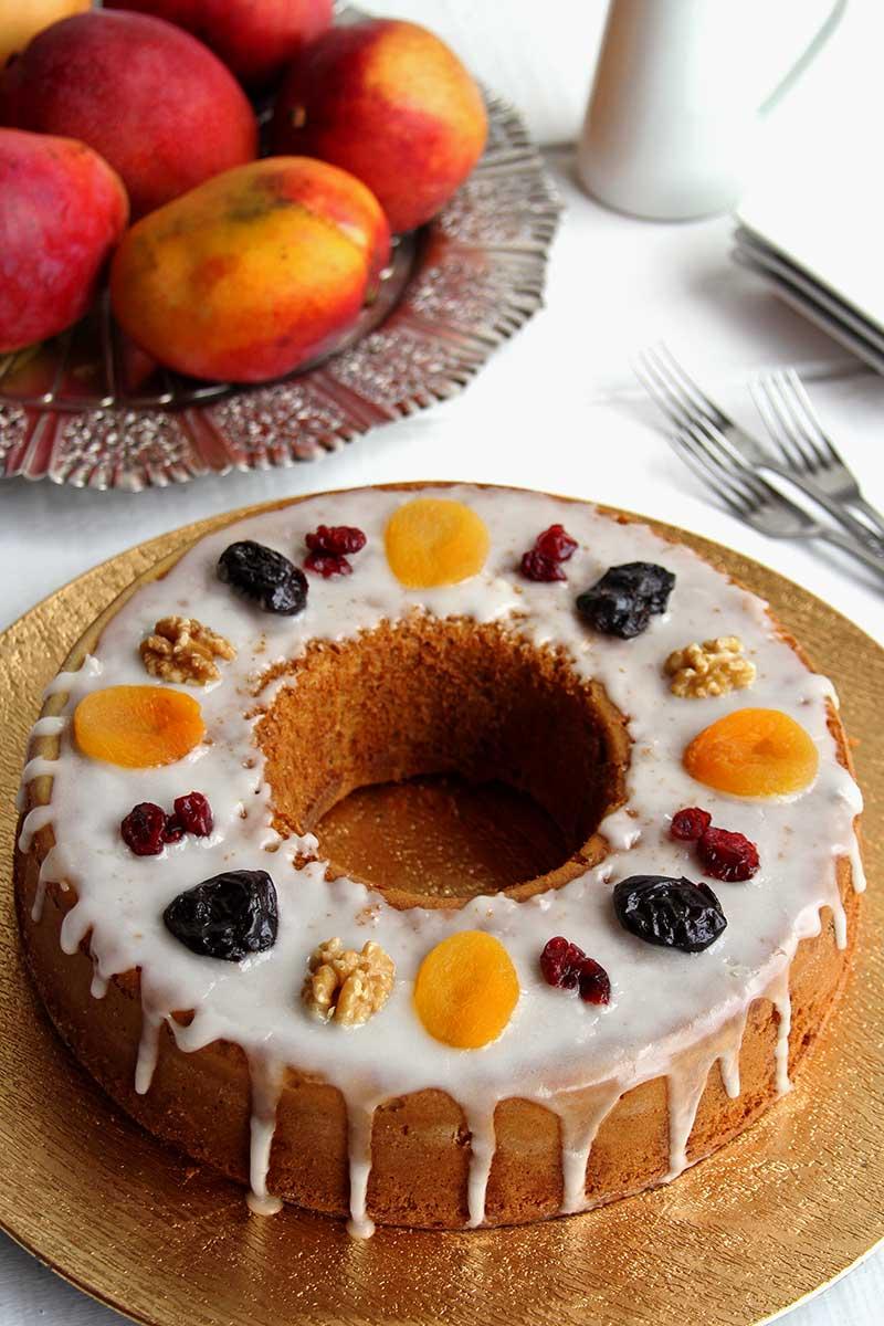 Bolo redondo com furo no meio decorado com glacê de açúcar e frutas secas