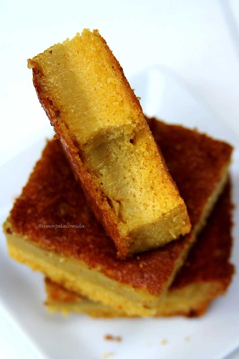 fatias sobrepostas de bolo de fubá cremoso, na parte de baixo do bolo uma camada de bolo fofinho, na parte de cima uma textura cremosa e aveludada