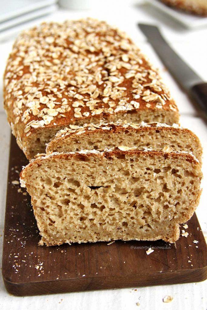 Pão de aveia fatiado na tábua de madeira sobre mesa branca