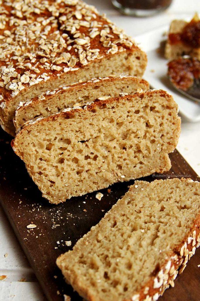 Pão de aveia fatiado sobre tábua de madeira escura e mesa branca