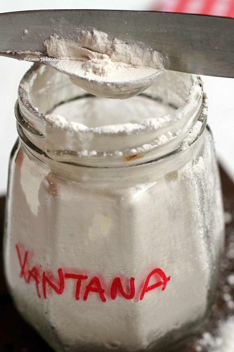 pó branco dentro vidro sendo medido com colher de chá