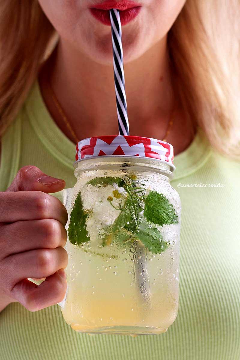 Mulher segurando copo de água com gás com limão e ervas