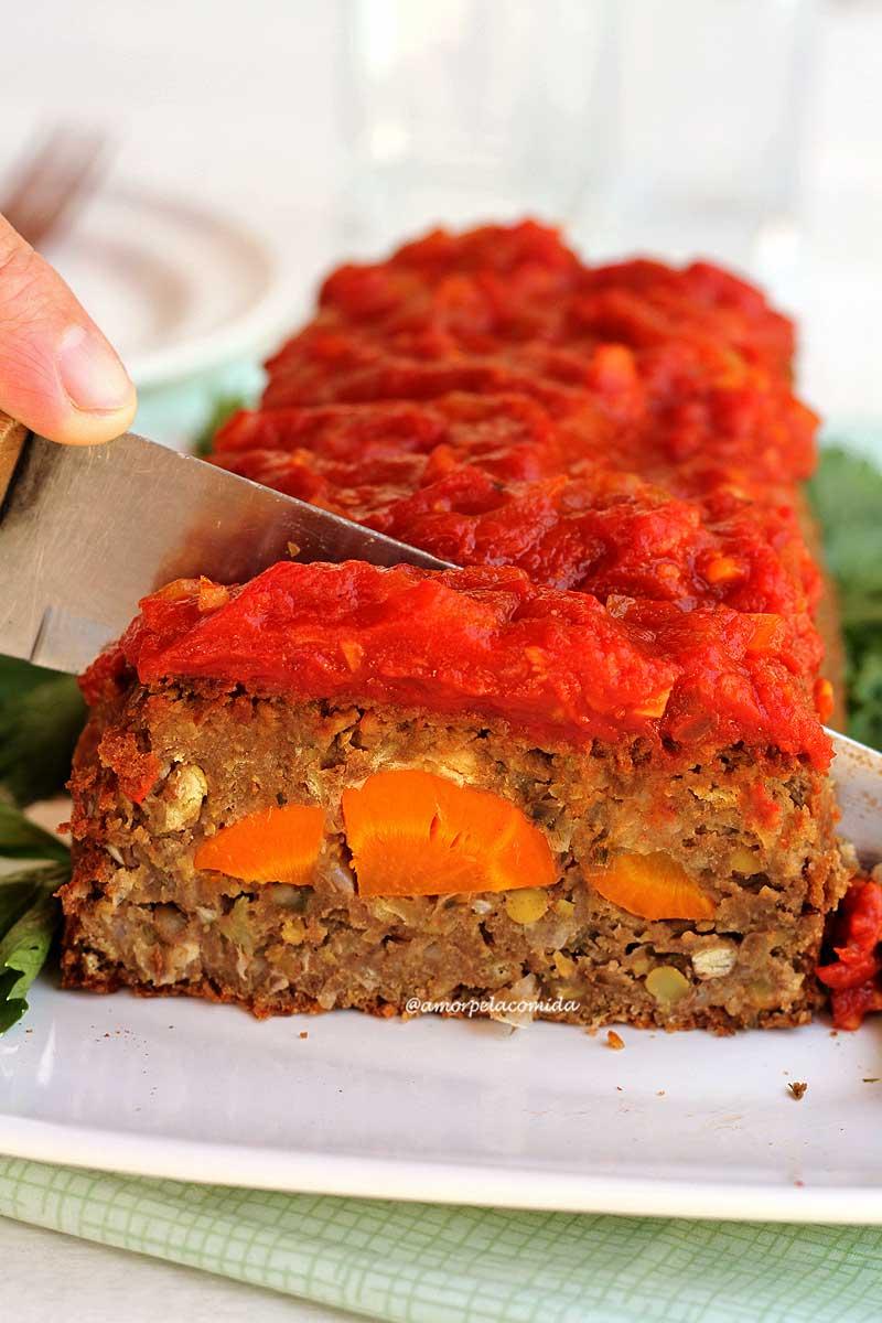 Bolo de carne vegetal recheado com cenoura sendo fatiado