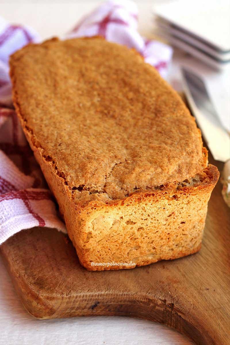 Pão de forma sobre tábua de madeira em uma mesa branca