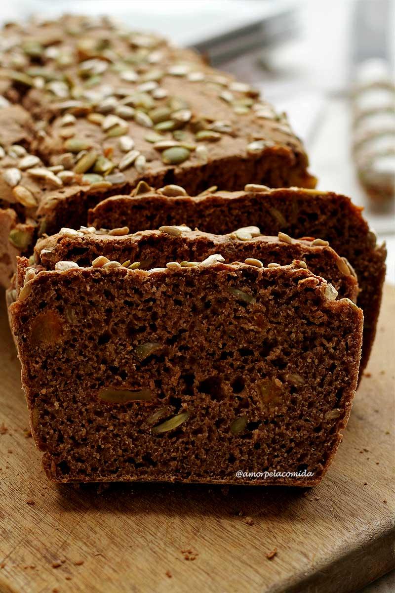Pão integral com sementes fatiado sobre tábua de madeira