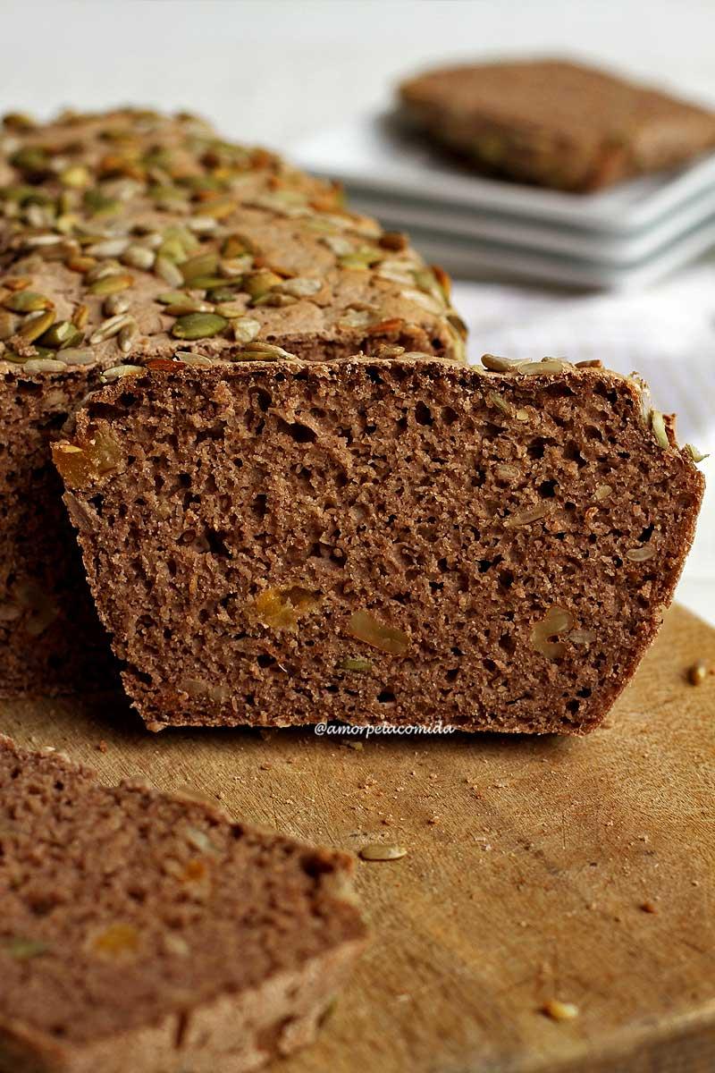 Fatia de pão integral com sementes sobre tábua de maneira em mesa branca