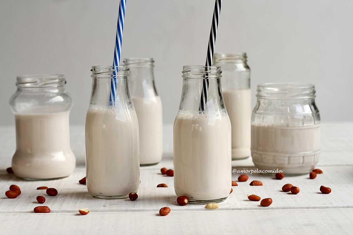 3 garrafinhas de vidro e 3 vidros de conserva reciclados com leite vegetal de amendoim sobre mesa branca