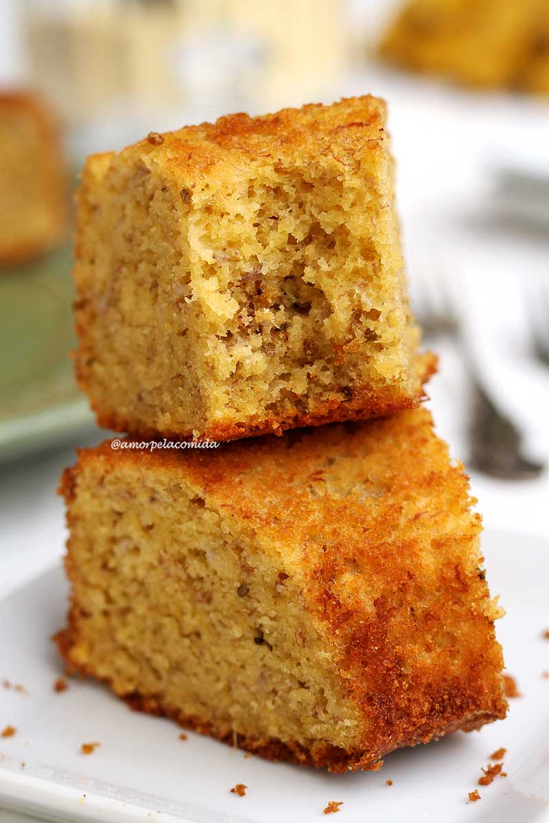 Duas fatias de bolo de fubá sobrepostas em um prato pequeno quadrado branco, a fatia de cima está mordida mostrando a textura aerada do bolo