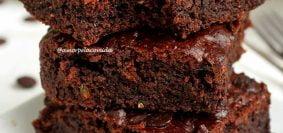 Três pedaços de brownie sobrepostos em um prato quadrado branco pequeno, o pedaço de cima está mordido e tem abobrinha ao fundo desfocadas