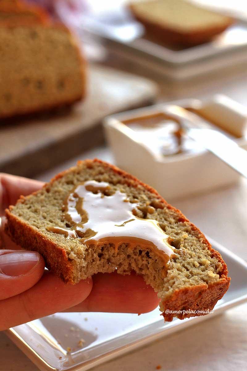 Mão segurando fatia de pão de batata mordida, sobre a fatia pasta de amendoim