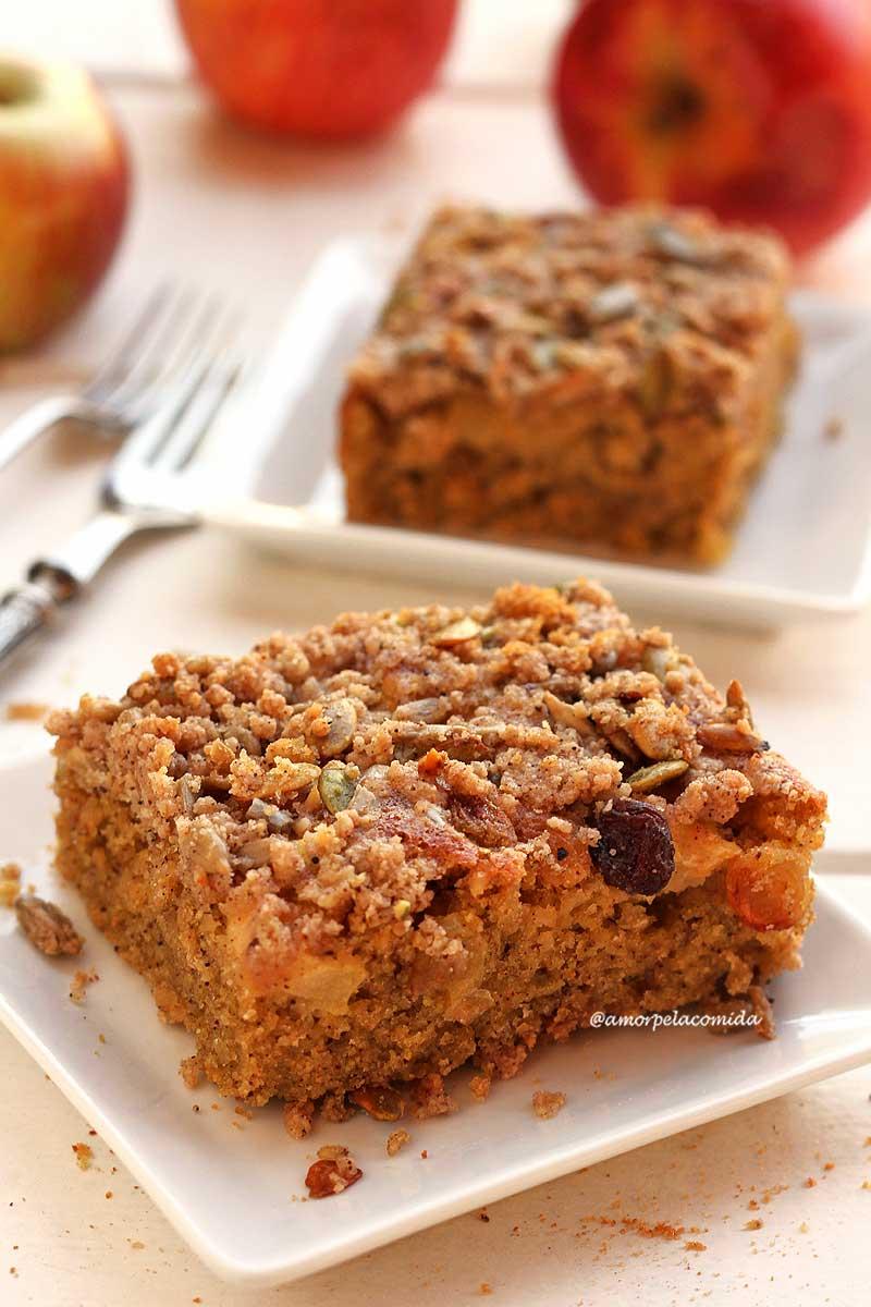 Dois pedaços de bolo de maçã com farofa em pratinhos quadrados brancos pequenos sobre mesa branca com maçãs ao fundo