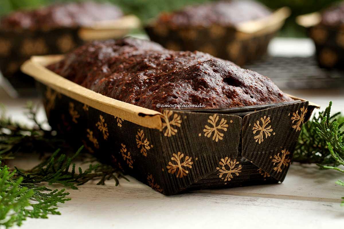 Chocotone dentro de uma forma de papelão marrom com detalhes em dourado sobre mesa branca decorada com ramos de cipreste