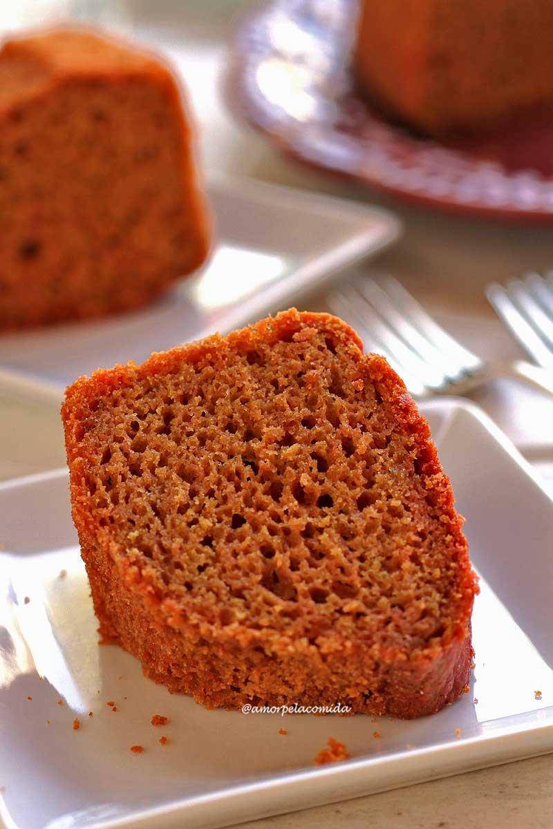Pedaço de bolo de beterraba sobre prato quadrado pequeno em uma mesa branca, ao fundo mais um pedaço de bolo e o bolo cortado, ambos estão desfocados