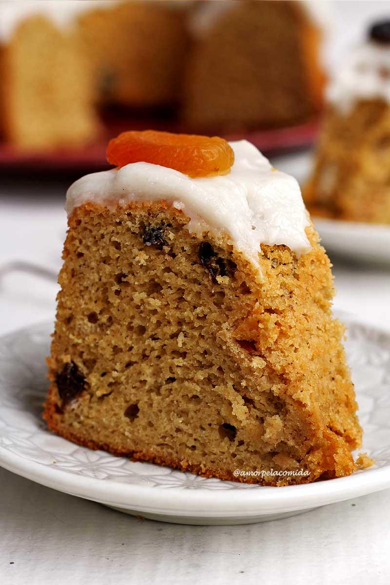 Pedaço de bolo de frutas com cobertura branca decorado com um damasco por cima sobre um prato redondo branco pequeno