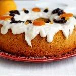 Bolo redondo com furo no meio decorado com cobertura branca que cai pela lateral com frutas secas no topo sobre prato cor de vinho em uma mesa branca