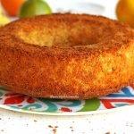 Bolo de fubá com laranja em banana redondo com furo no meio sobre prato estampado em uma mesa branca, ao fundo banana e laranja desfocados