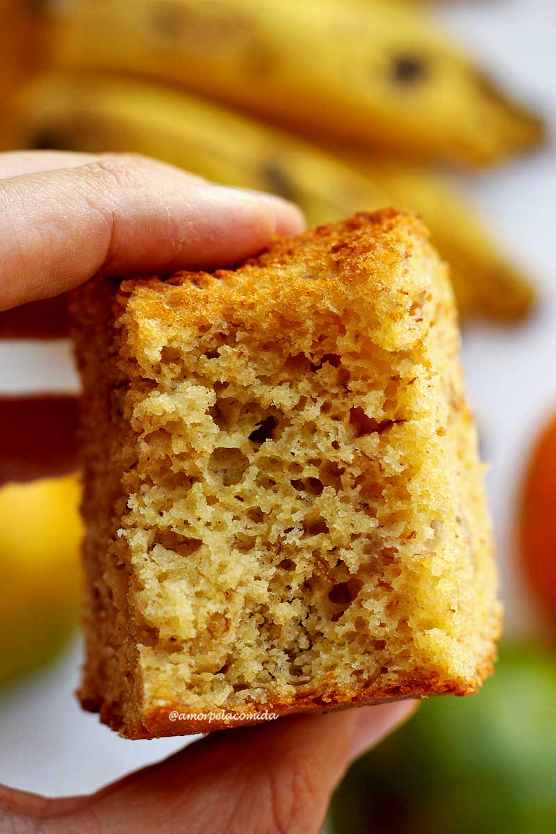 Pedaço de bolo de fubá com laranja e banana mordido sendo segurado por uma mão, ao fundo bananas e laranjas desfocadas em uma mesa branca