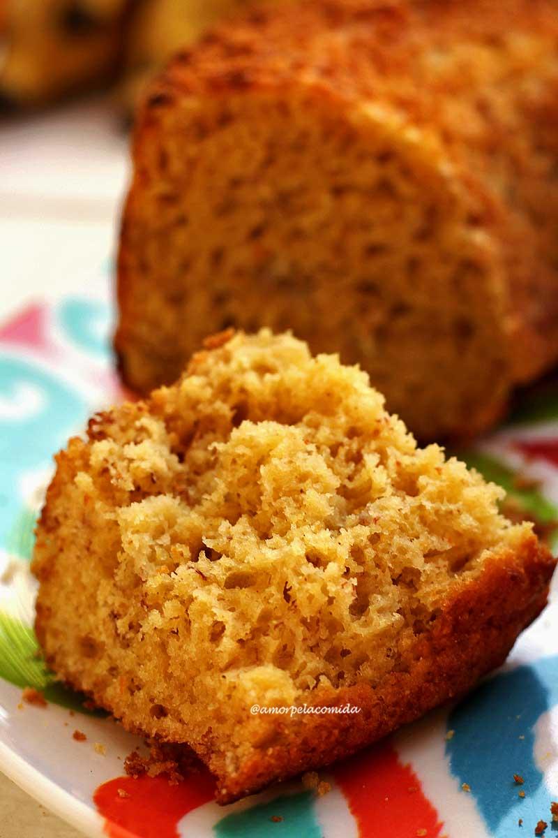Pedaço de bolo partido sobre prato estampado colorido, a foto mostra a textura bem aerada da massa e ao fundo está o bolo desfocado