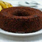 Bolo redondo com furo no meio de banana com chocolate sobre um prato branco, ao fundo bananas desfocadas e pratinhos pequenos desfocados