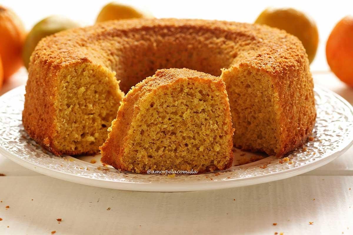 Bolo de laranja redondo com furo no meio partido sobre um prato branco, no meio do bolo tem uma fatia mostrando a textura aerada da massa, ao fundo laranjas desfocadas em uma mesa branca