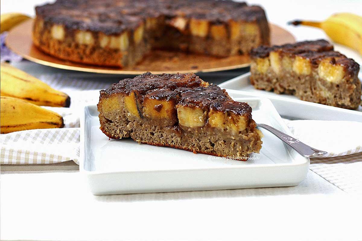 Fatia triangula de bolo de banana caramelizado na superfície, ao lado mais uma fatia de bolo e ao fundo o bolo partido em uma mesa branca