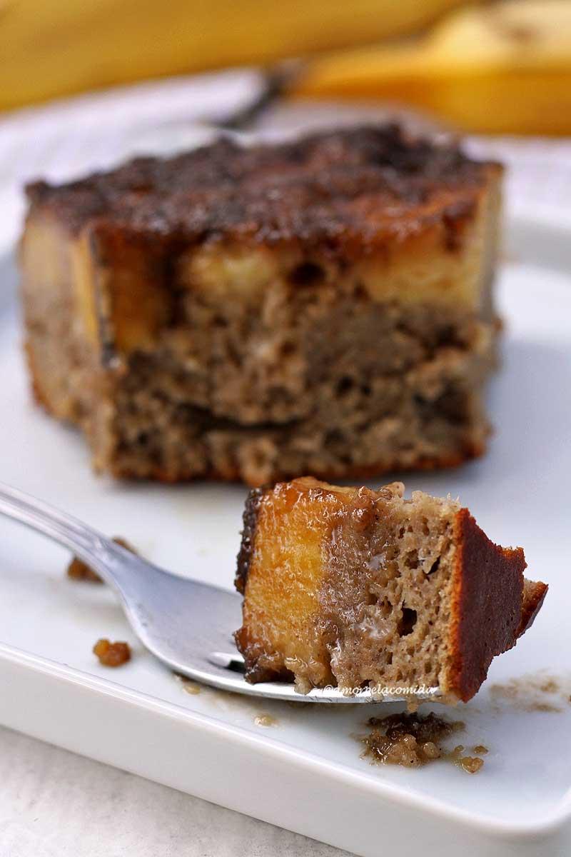 Garfo apoiado em um prato branco com uma garfada de bolo de banana caramelizada, ao fundo o restante da fatia desfocada