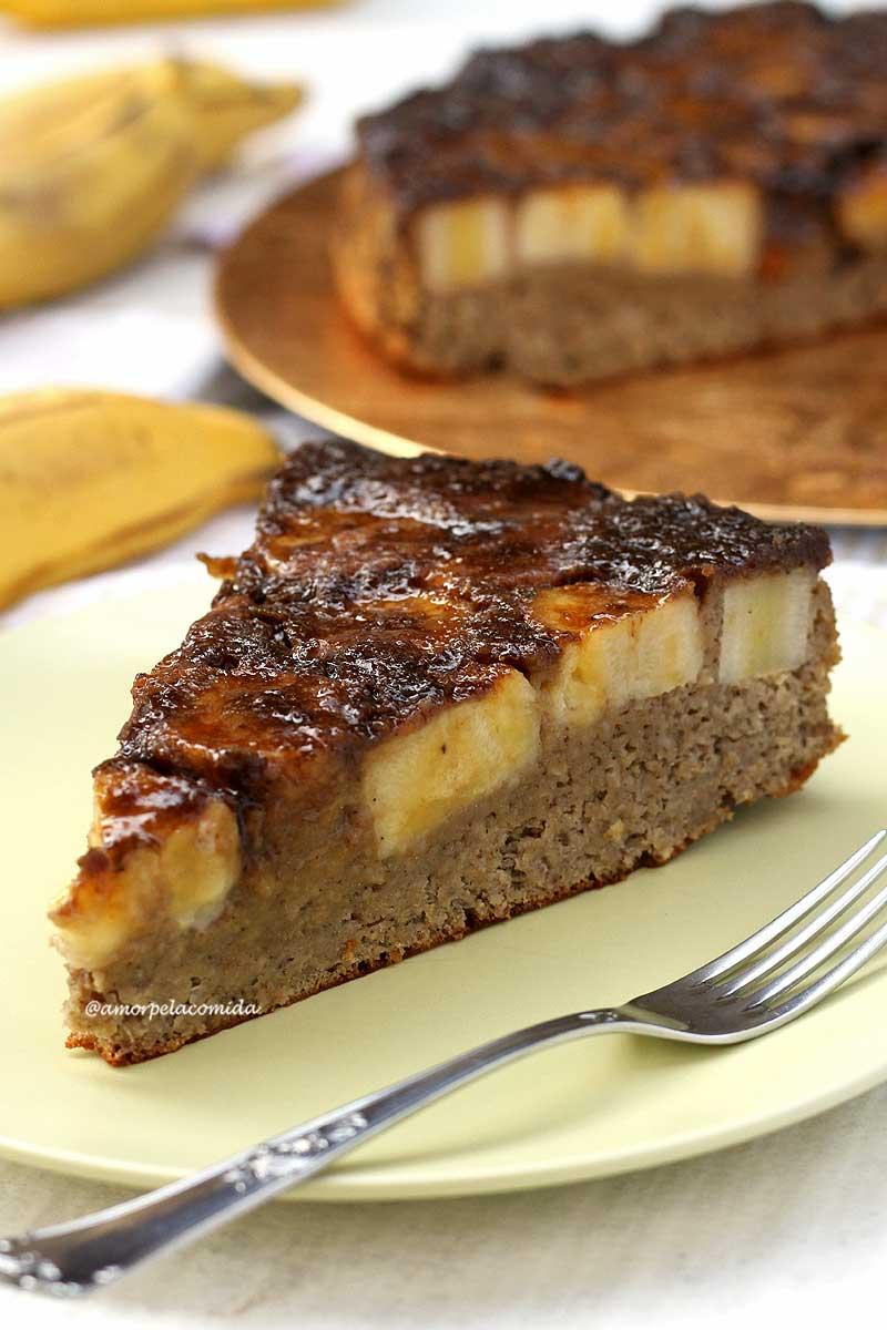 Fatia triangulas de bolo de banana com cobertura de banana caramelizada, ao fundo o bolo partido e algumas bananas em uma mesa branca