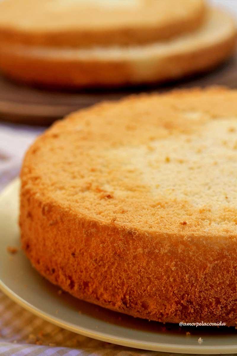 Bolo pão de ló redondo sobre prato verde claro, ao fundo mais um pão de ló sobre uma tábua de madeira
