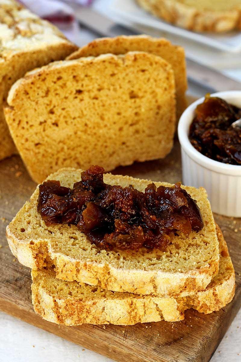 Duas fatias sobrepostas em uma tábua de madeira, a fatia de cima tem geleia de figo em pedaços, ao fundo mais duas fatias cortadas apoiadas no pão de milho, ao lado um pote branco pequeno com geleia de figo