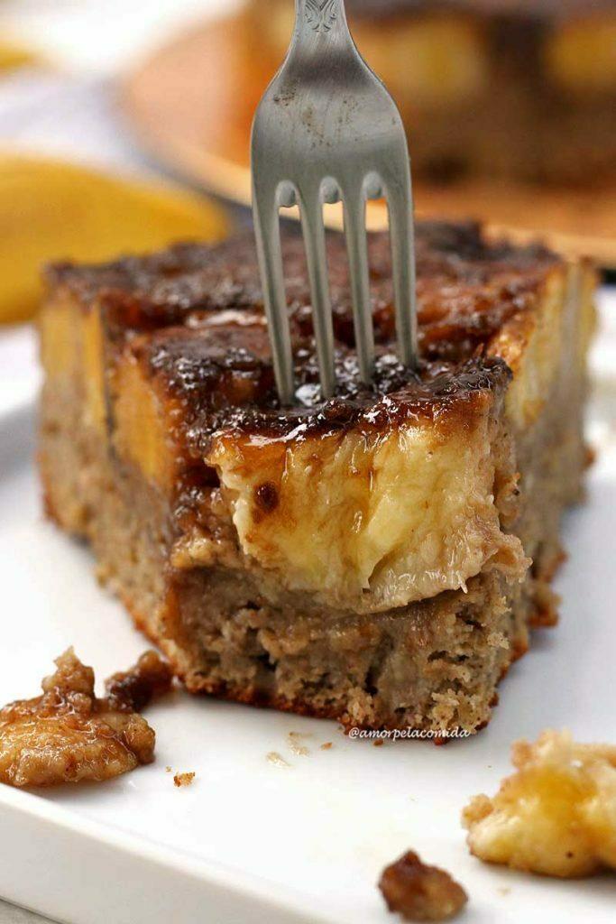 Fatia de bolo com bananas caramelizadas no topo, a fatia já está faltando uma garfada e na foto tem um garfo indicando onde será a próxima garfada
