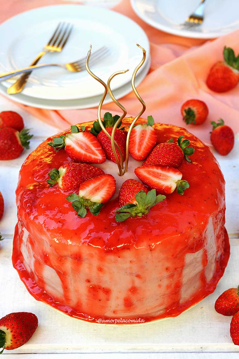 Bolo redondo de morango, no topo do bolo tem uma cobertura vermelha a base de morangos e morango cortados ao meio decorando o topo