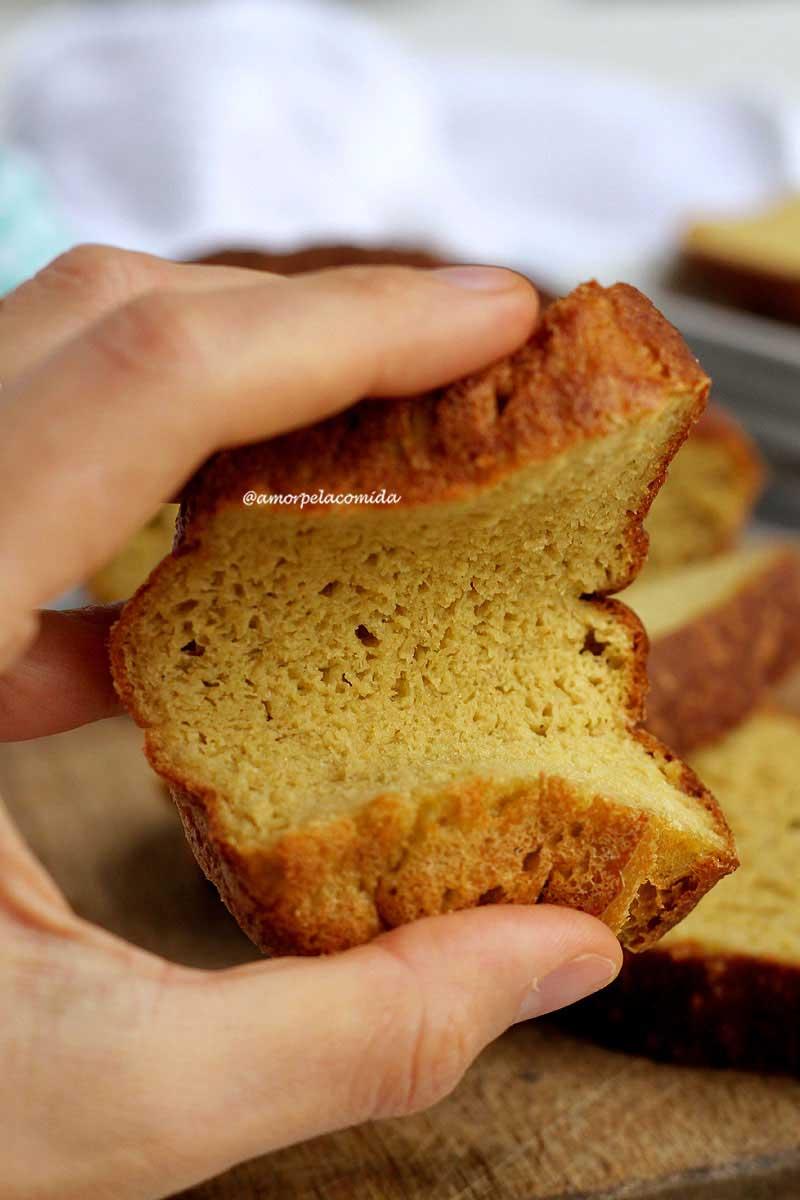 Mão segurando fatia de pão caseiro sendo pressionada pelas duas extremidades da fatia para mostrar a flexibilidade da fatia
