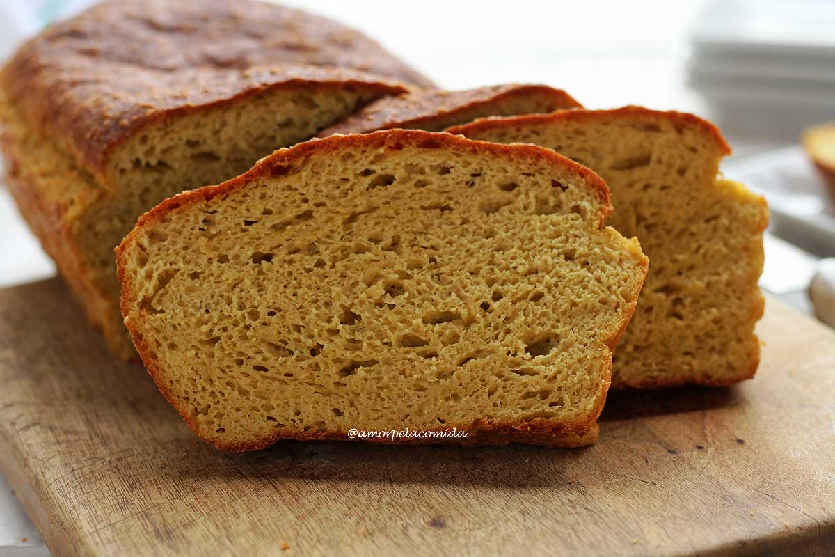 Pão caseiro fatiado, são três fatias apoiadas no pão sobre uma tábua de madeira em uma mesa branca
