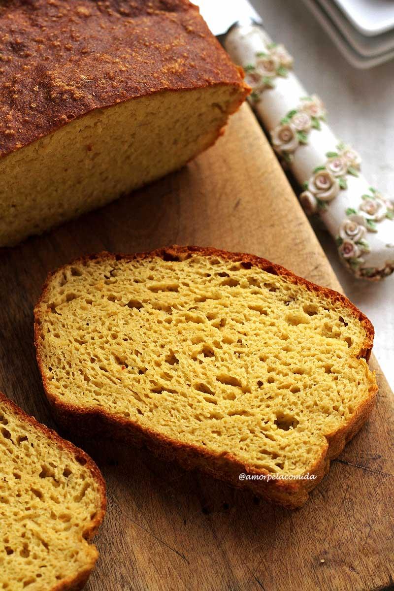 fatia de pão caseiro sobre tábua de madeira em uma mesa branca