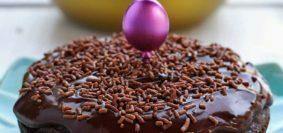 Bolo de chocolate redondo pequeno sobre prato azul turquesa, ao fundo uma frigideira amarela desfocada