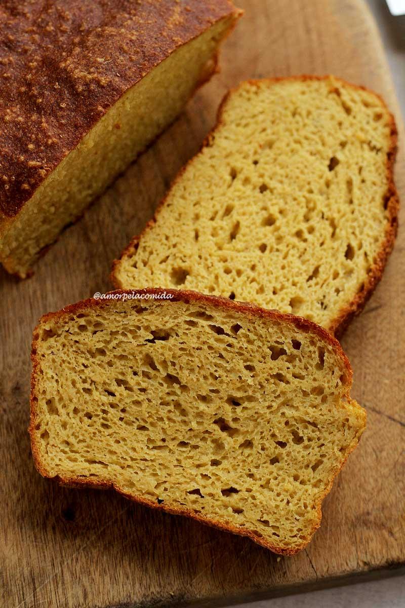 Duas fatias de pão caseiro sobrepostas em uma tábua de madeira ao lado do pão cortado