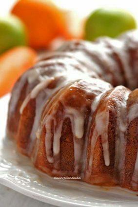 Bolo redondo com furo no meio coberto de glacê de açúcar ao fundo laranjas e cenouras desfocadas